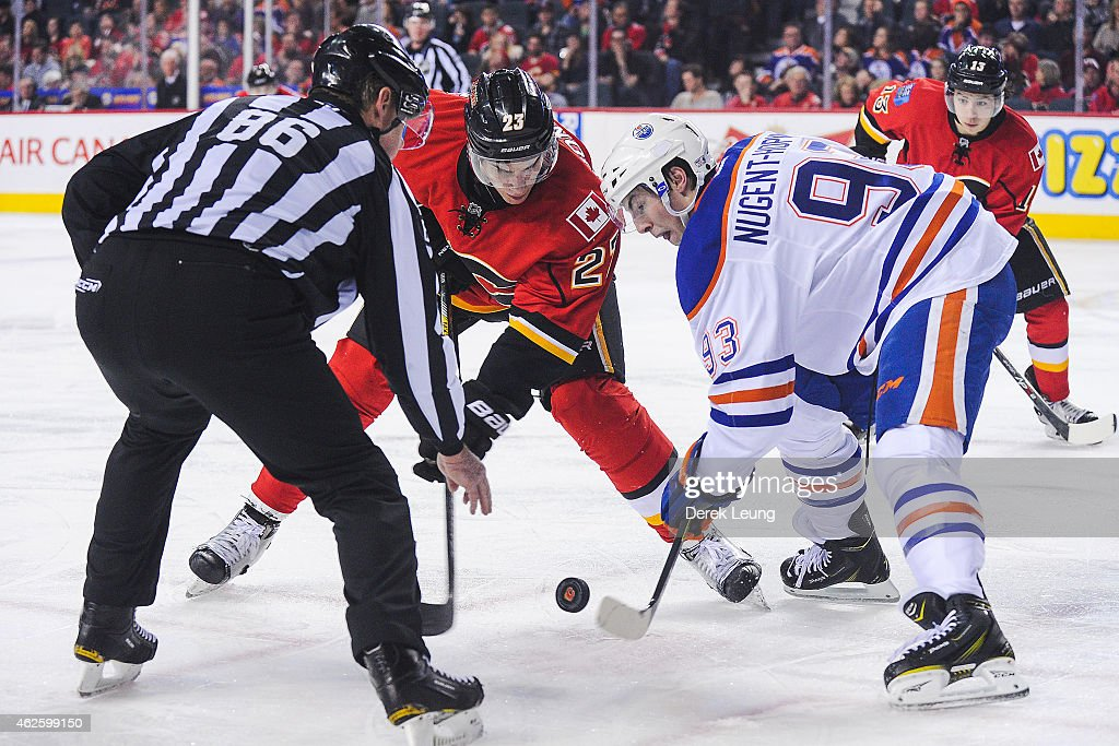 Sean Monahan #23 of the Calgary Flames faces-off against Ryan Nugent-Hopkins #93 of the Edmonton Oilers during an NHL game at Scotiabank Saddledome on January 31, 2015 in Calgary, Alberta, Canada. The Flames defeated the Oilers 4-2.