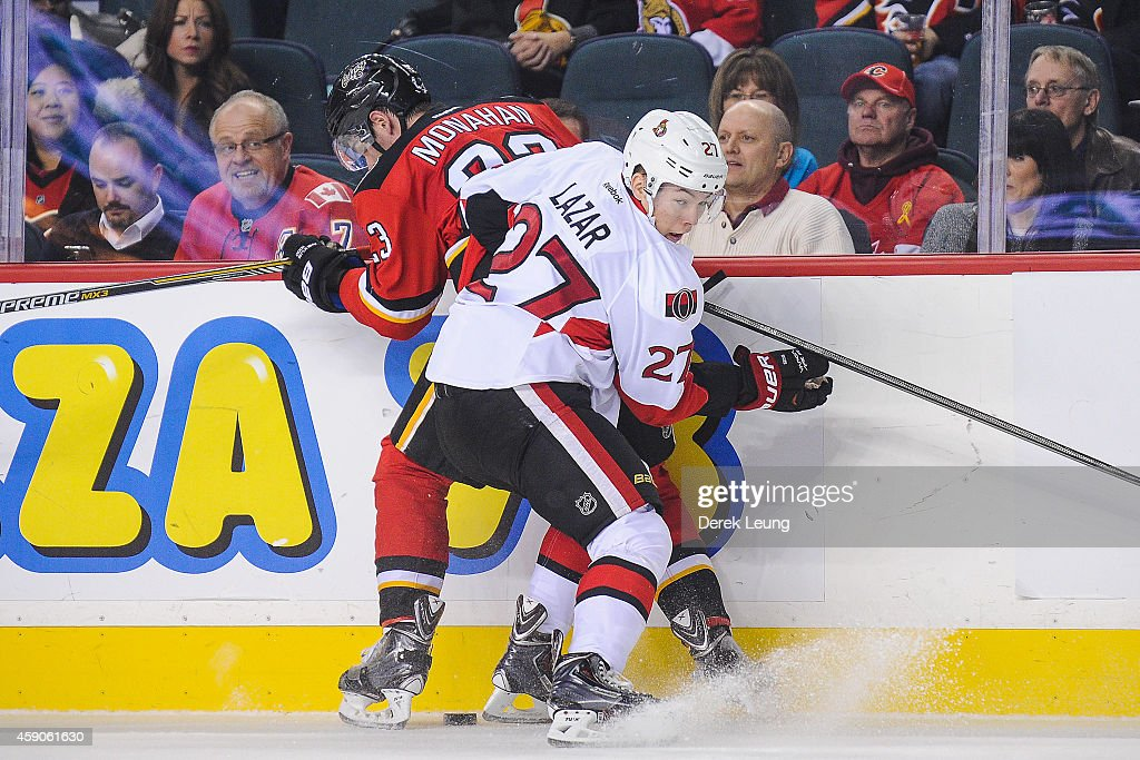 Sean Monahan #23 of the Calgary Flames is checked by Curtis Lazar #27 of the Ottawa Senators during an NHL game at Scotiabank Saddledome on November 15, 2014 in Calgary, Alberta, Canada. The Flames defeated the Senators 4-2.