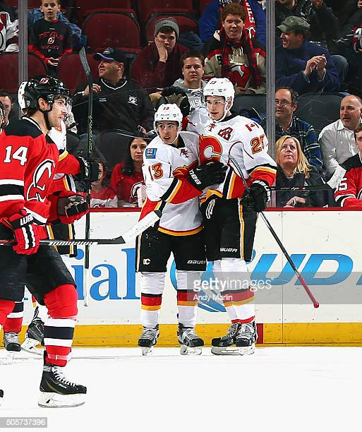 Sean Monahan of the Calgary Flames is congratulated by teammate Johnny Gaudreau after scoring a firstperiod goal as Adam Henrqiue of the New Jersey...