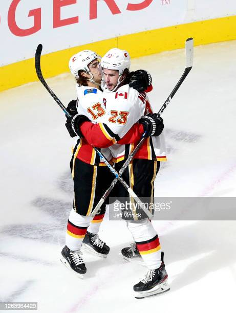 Sean Monahan of the Calgary Flames is congratulated by teammate Johnny Gaudreau after he scored a goal in the second period against the Winnipeg Jets...