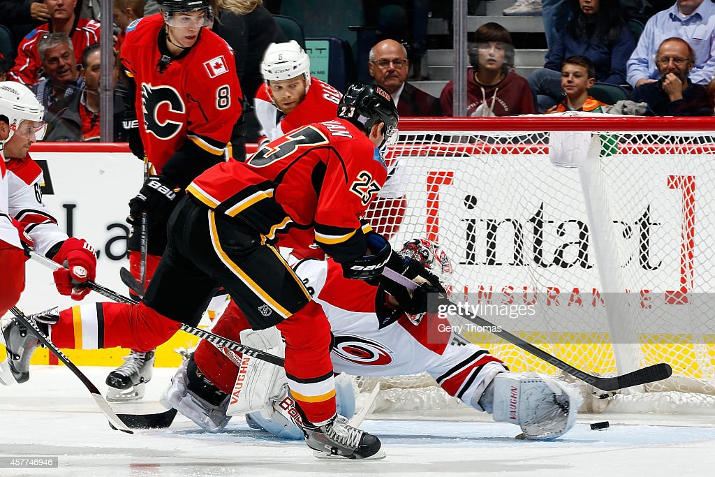 Sean Monahan #23 of the Calgary Flames scores on a backhand against Cam Ward #30 of the Carolina Hurricanes at Scotiabank Saddledome on October 23, 2014 in Calgary, Alberta, Canada.
