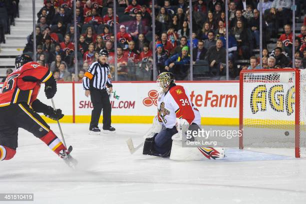 Sean Monahan of the Calgary Flames shoots the puck past Tim Thomas of the Florida Panthers during shootout during an NHL game at Scotiabank...