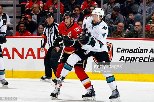 Sean Monahan of the Calgary Flames skates against Brenden Dillon of the San Jose Sharks during an NHL game on January 11 2017 at the Scotiabank...