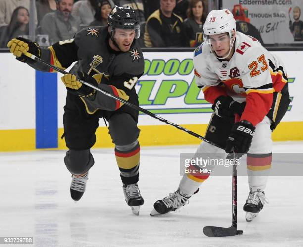 Sean Monahan of the Calgary Flames skates with the puck against Brayden McNabb of the Vegas Golden Knights in the first period of their game at...