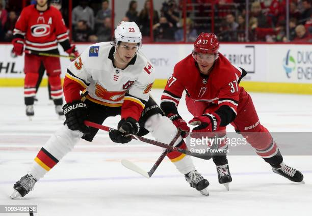 Sean Monahan of the Calgary Flames steers the puck away from the defense of Andrei Svechnikov of the Carolina Hurricanes during an NHL game on...