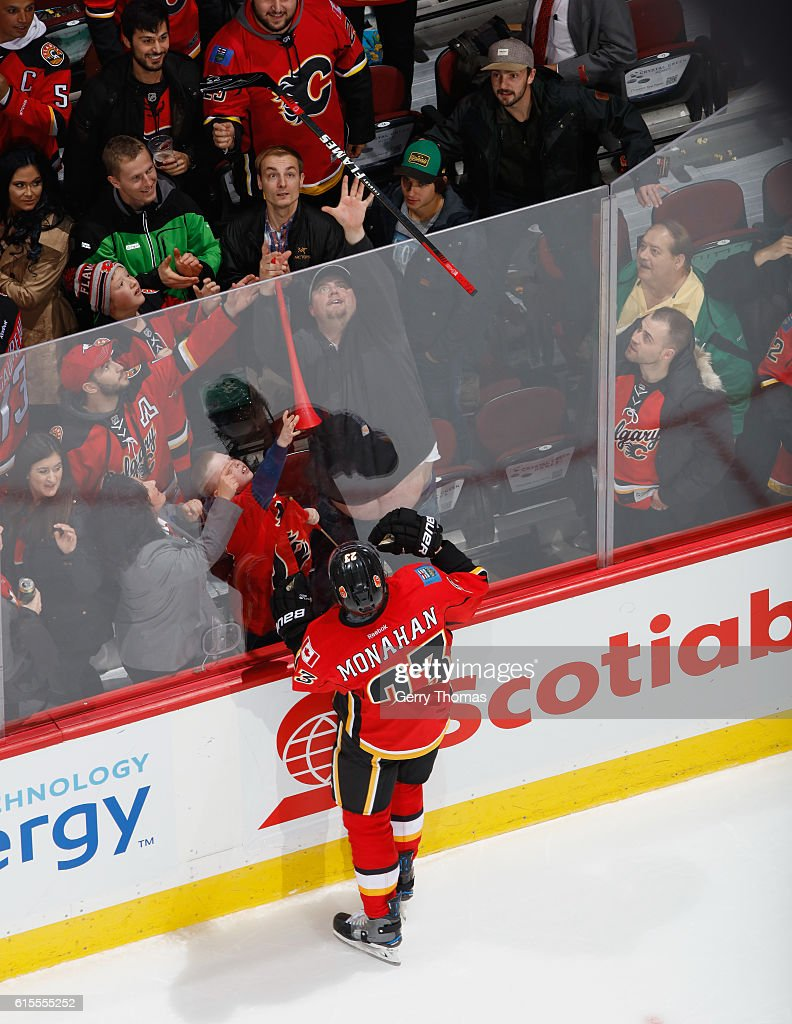 Sean Monahan #23 of the Calgary Flames toss a stick to some lucky fans after the game against the Buffalo Sabres at Scotiabank Saddledome on October 18, 2016 in Calgary, Alberta, Canada.