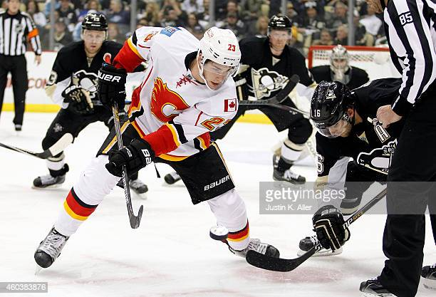 Sean Monahan of the Calgary Flames wins a face-off against Brandon Sutter of the Pittsburgh Penguins in the second period during the game at Consol...