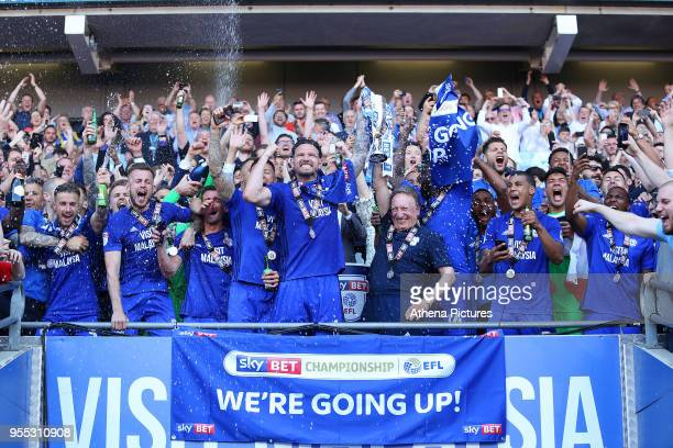 Sean Morrison of Cardiff City and Cardiff City manager Neil Warnock lift the trophy after being automatically promoted to the Premier League after...