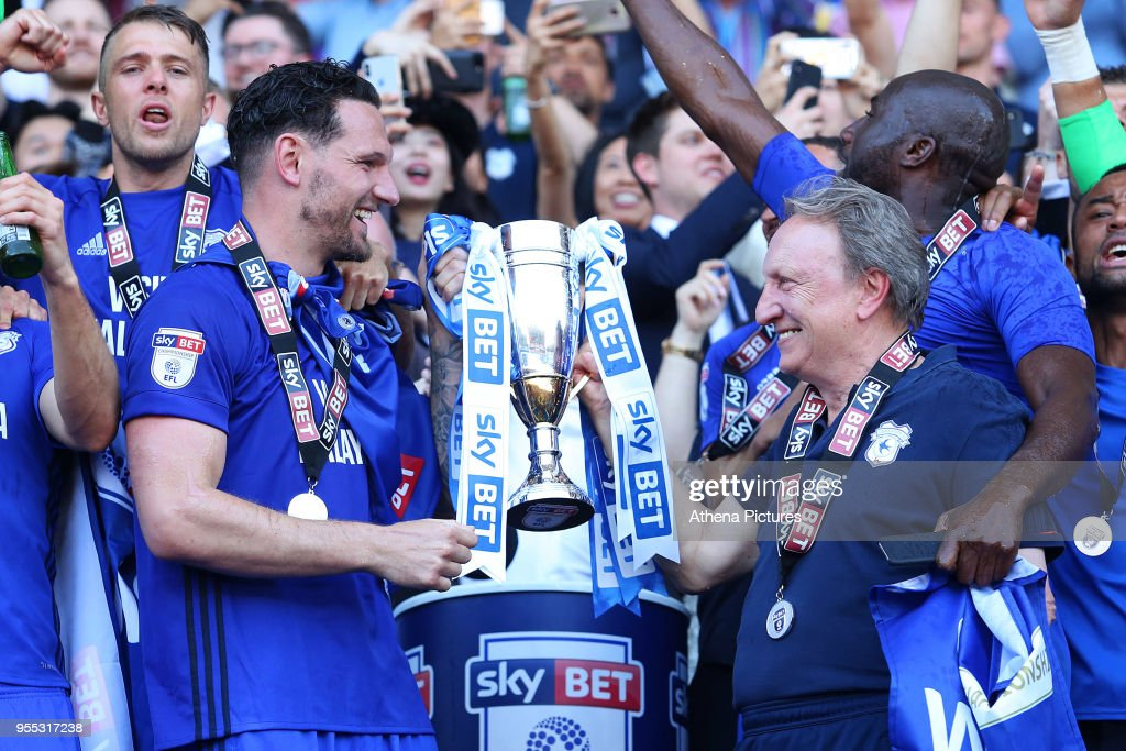 Sean Morrison of Cardiff City and Cardiff City manager Neil Warnock laugh as they lift the trophy after being automatically promoted to the Premier League after the final whistle of the Sky Bet Championship match between Cardiff City and Reading at The Cardiff City Stadium on May 06, 2018 in Cardiff, Wales.