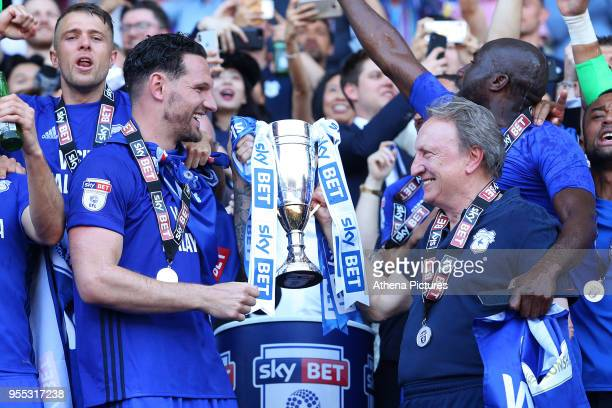 Sean Morrison of Cardiff City and Cardiff City manager Neil Warnock laugh as they lift the trophy after being automatically promoted to the Premier...