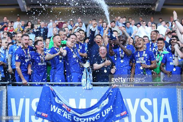 Sean Morrison of Cardiff City lifts the trophy as Sol Bamba sprays champagne over Cardiff City manager Neil Warnock and Cardiff as they celebrate...