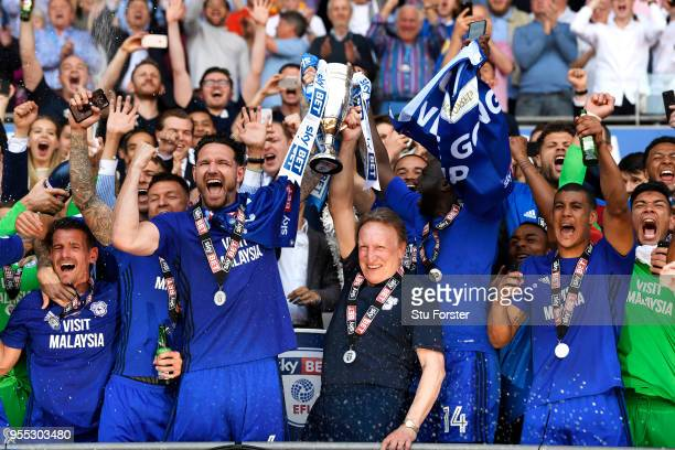 Sean Morrison of Cardiff City lifts the trophy with Neil Warnock Manager of Cardiff City as they celebrate gaining promotion back to the premier...