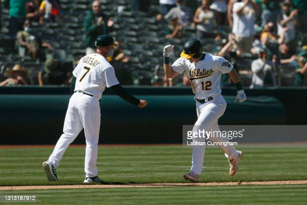 Sean Murphy of the Oakland Athletics celebrates with third base coach Mark Kotsay as he rounds the bases after hitting a solo home run in the bottom...