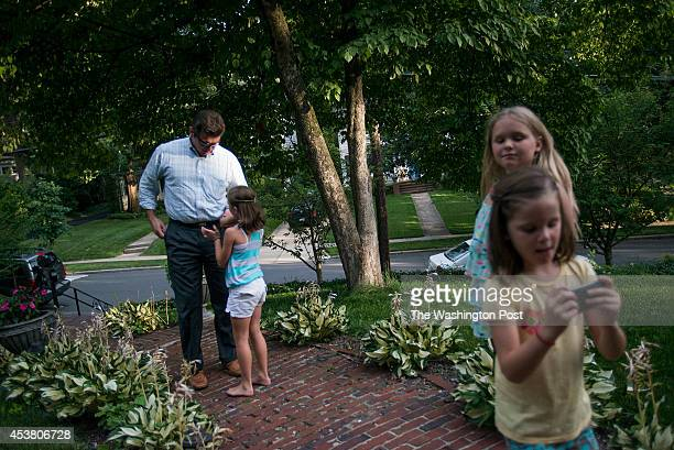 Sean Murray listens to Quinn Murray when he gets home from work while Kylie Squier a neighbor hangs out with Coco Murray on Thursday July 24 2014 in...