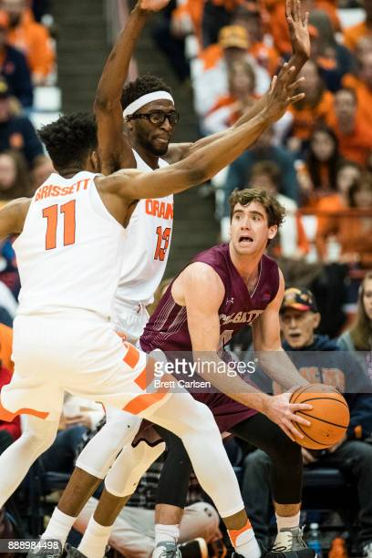 Sean O'Brien of the Colgate Raiders is trapped in the corner by Oshae Brissett and Paschal Chukwu of the Syracuse Orange during the second half at...