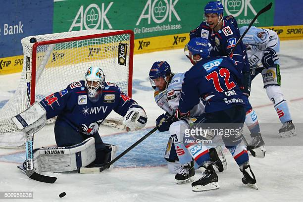 Sean O'Connor of Straubing is challenged by goalkeeper Dennis Endras and Mathieu Carle of Mannheim during the DEL match between Adler Mannheim and...