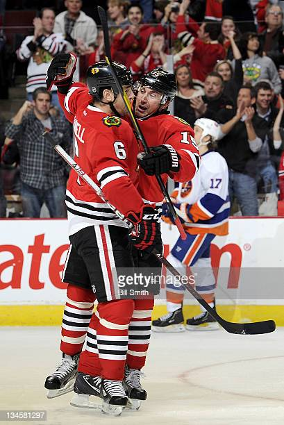 Sean O'Donnell and Andrew Brunette of the Chicago Blackhawks hug after Brunette scored against the New York Islanders during the NHL game on December...