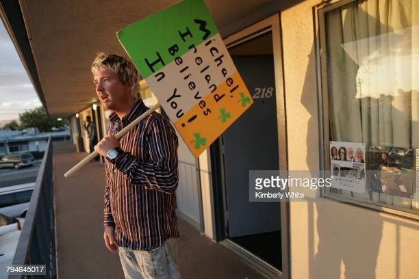 Sean O'Kane from Ireland yells to a friend outside his hotel room after a day of rallying support for pop singer Michael Jackson in Santa Maria...