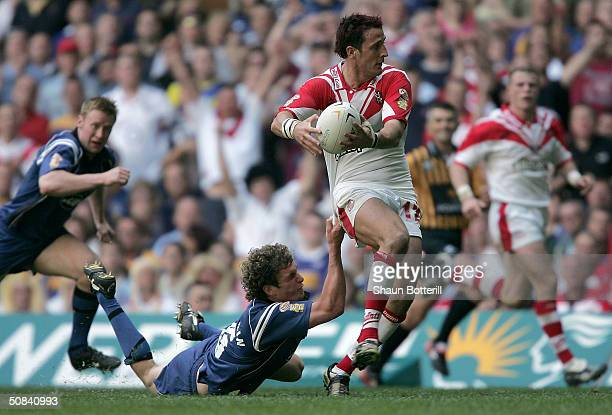 Sean O'Loughlin of Wigan Warriors tries to tackle Lee Gilmour of St. Helens during the Powergen Challenge Cup Final match between St. Helens and...