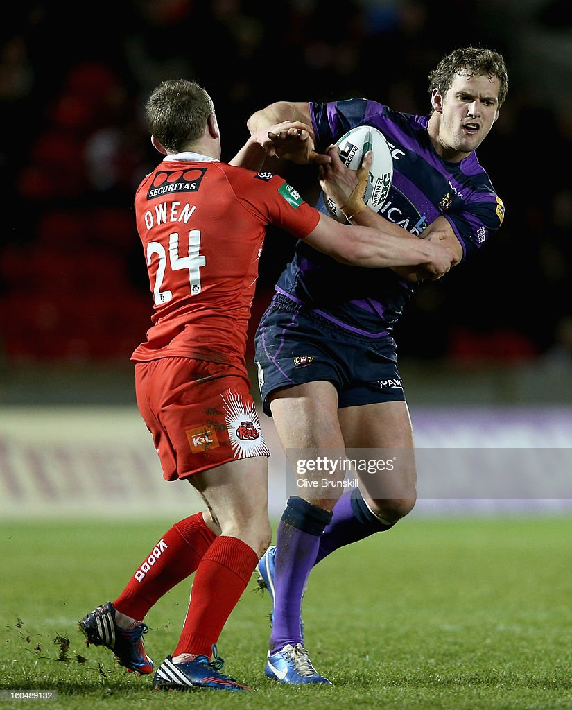 Sean O'Loughlin of Wigan Warriorsis tackled by Gareth Owen of Salford City Reds during the Super League match between Salford City Reds and Wigan Warriors at Salford City Stadium on February 1, 2013 in Salford, England.
