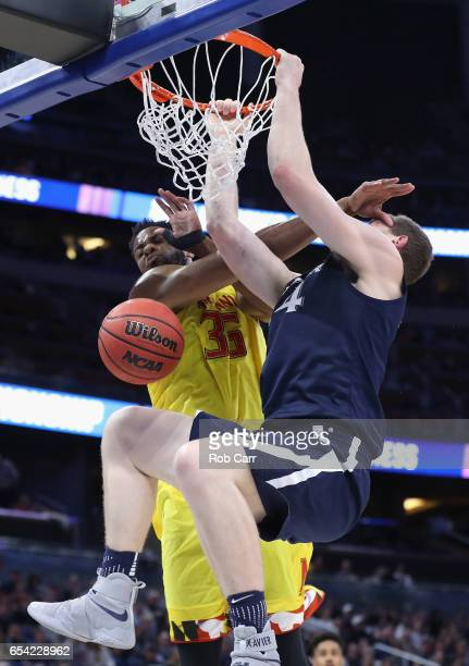 Sean O'Mara of the Xavier Musketeers dunks the ball against Damonte Dodd of the Maryland Terrapins in the first half during the first round of the...