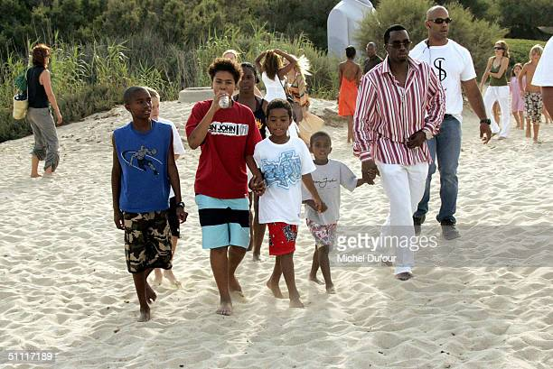 Sean 'P Diddy' Combs holds hands with his son on Pampelonne Beach during lunch at Le Club 55 July 26 2004 in Saint Tropez France