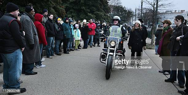Sean Patton a motorcycle officer for the US Capitol Police yells instructions to people lined up outside the Dirksen Building on Constitution Avenue...