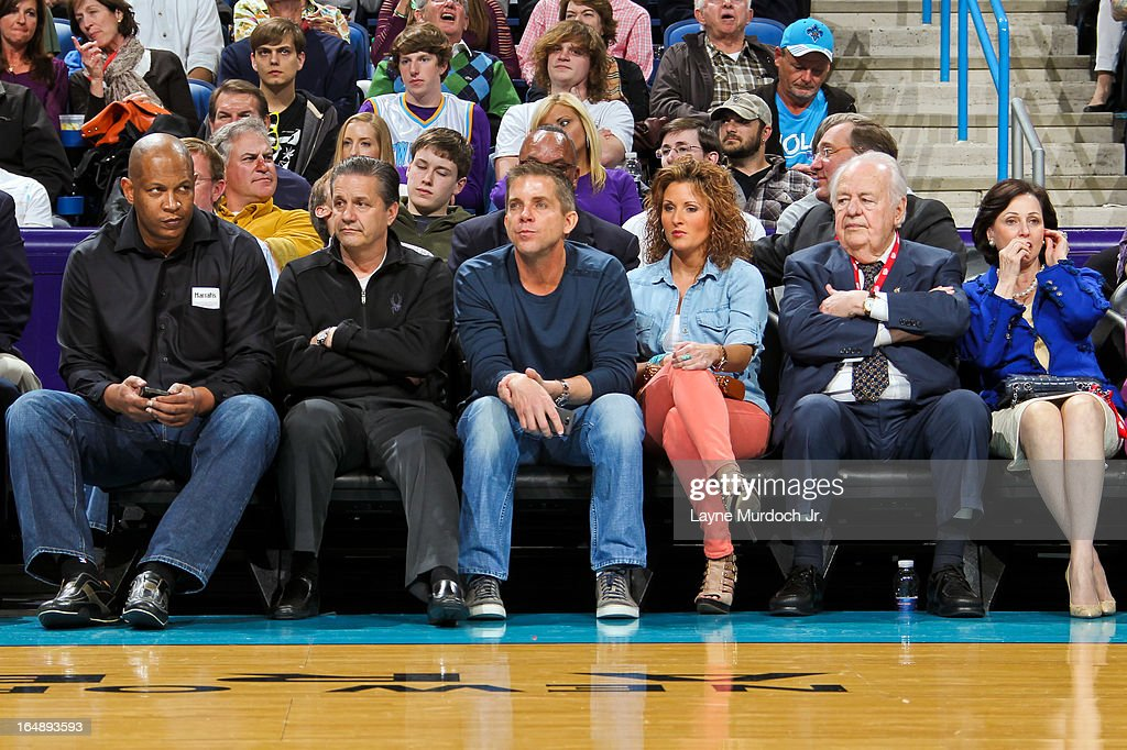 Sean Payton, head coach of the New Orleans Saints, center, John Calipari, head coach of the University of Kentucky basketball team, second left, and Tom Benson, owner of the Saints and New Orleans Hornets, second right, attend an NBA game between the Los Angeles Clippers and Hornets on March 27, 2013 at the New Orleans Arena in New Orleans, Louisiana.