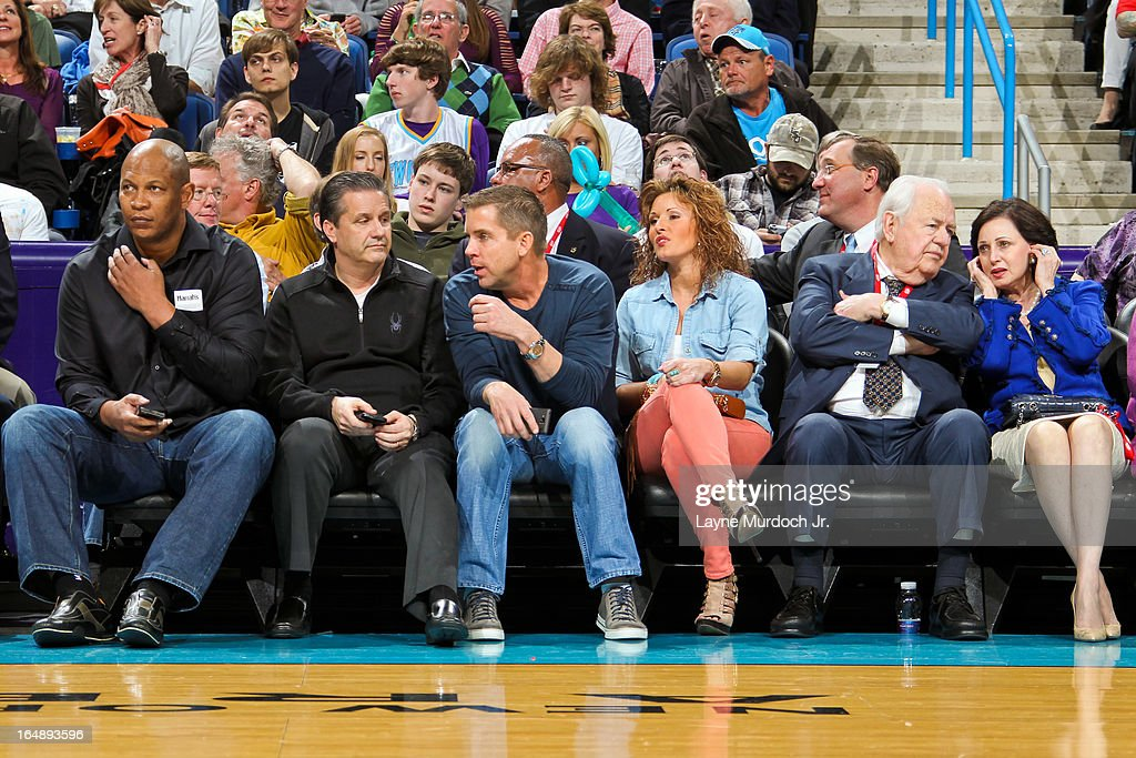 Sean Payton, head coach of the New Orleans Saints, center, speaks with John Calipari, head coach of the University of Kentucky basketball team, second left, as Tom Benson, owner of the Saints and New Orleans Hornets sits second right during an NBA game between the Los Angeles Clippers and Hornets on March 27, 2013 at the New Orleans Arena in New Orleans, Louisiana.