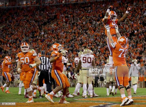 Sean Pollard holds up teammate Travis Etienne of the Clemson Tigers after he scores a touchdown against the Florida State Seminoles during their game...