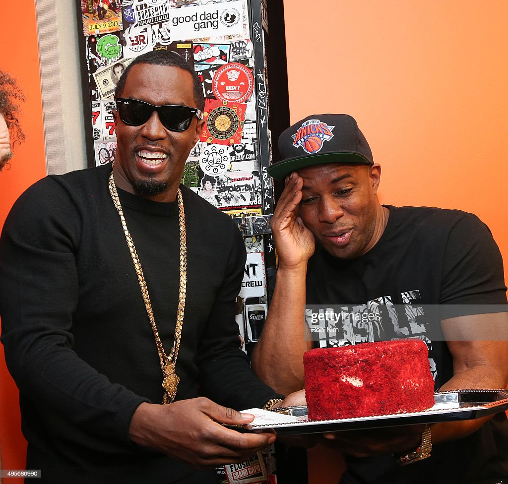 Sean 'Puff Diddy' Combs (L) and DJ Whoo Kid hold a cake for Sean's birthday at SiriusXM Studios on November 4, 2015 in New York City.