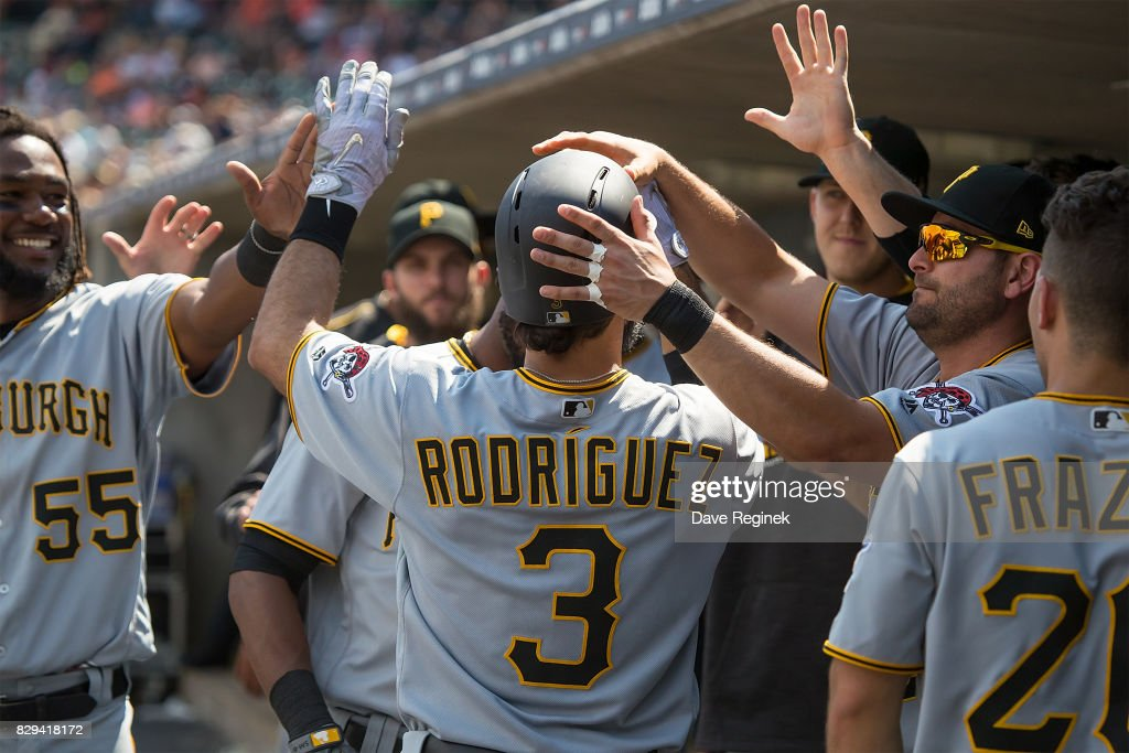 Sean Rodriguez #3 of the Pittsburgh Pirates hi-fives teammates in the dugout after hitting a solo home run in the eighth inning against the Detroit Tigers during a MLB game at Comerica Park on August 10, 2017 in Detroit, Michigan. The Pirates defeated the Tigers 7-5.