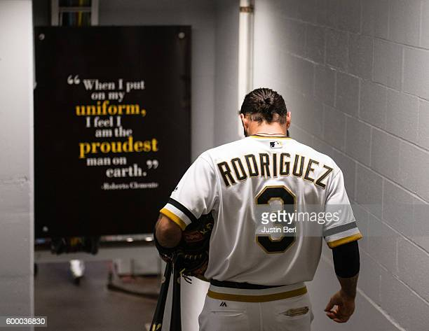 Sean Rodriguez of the Pittsburgh Pirates walks past a sign honoring Roberto Clemente as he heads to the dugout before the start of the game against...