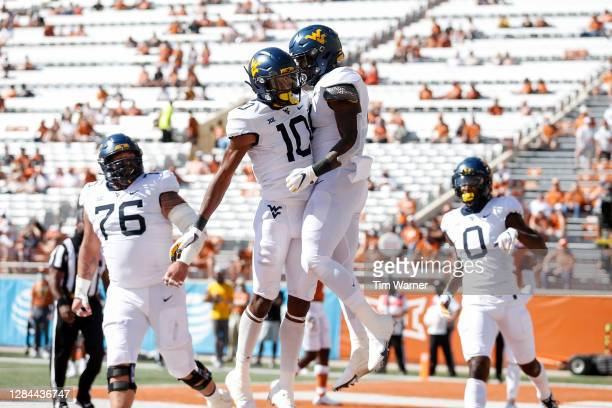 Sean Ryan of the West Virginia Mountaineers congratulates Leddie Brown after a touchdown in the first quarter against the Texas Longhorns at Darrell...