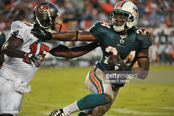 Sean Smith of the Miami Dolphins intercepts a pass and pushes away Reggie Brown of the Tampa Bay Buccaneers during a NFL preseason game at Sun Life...