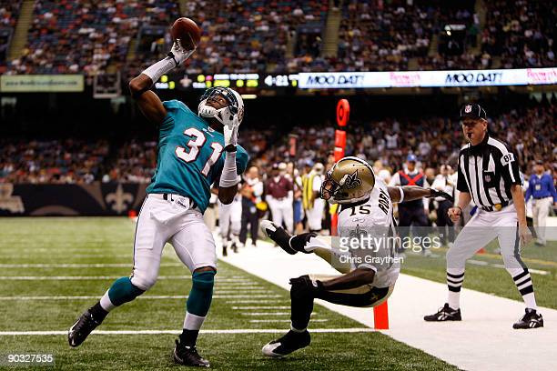 Sean Smith of the Miami Dolphins makes an interception catch over Courtney Roby of the New Orleans Saints at the Louisiana Superdome on September 3...