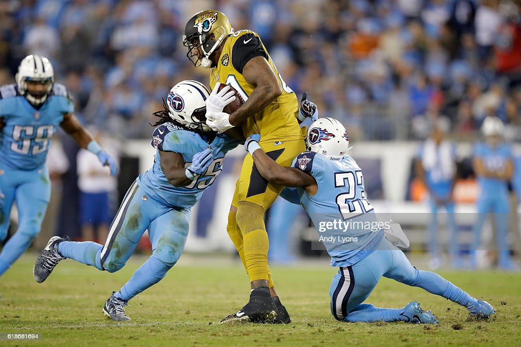 Sean Spence #55 and Brice McCain #23 of the Tennessee Titans tackle Marcedes Lewis #89 of the Jacksonville Jaguars at Nissan Stadium on October 27, 2016 in Nashville, Tennessee.