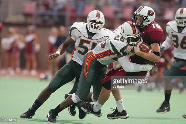 Sean Taylor of the Miami Hurricanes tackles quarterback Mike McGann of the Temple Owls during the NCAA football game at Franklin Field in...