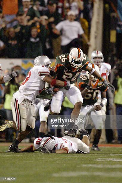 Sean Taylor of the University of Miami Hurricanes fights off the tackle by Maurice Clarett of the Ohio State Buckeyes just before losing the football...