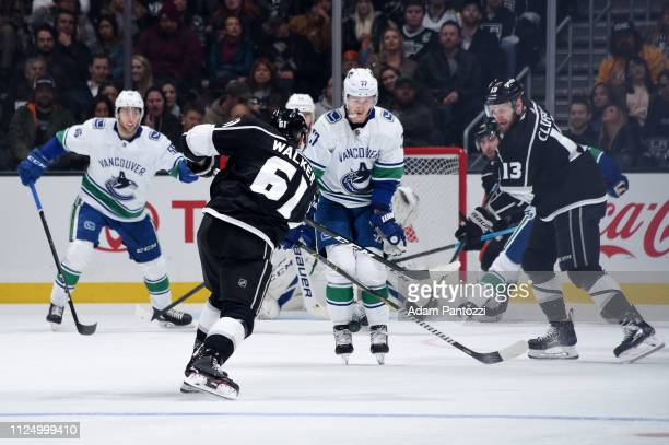Sean Walker takes a shot that is blocked by Nikolay Goldobin of the Vancouver Canucks as Kyle Clifford of the Los Angeles Kings looks on during the...