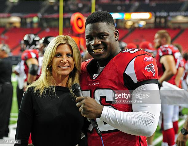 Sean Weatherspoon of the Atlanta Falcons poses with Laura Okmin of Fox Sports after the game against the Baltimore Ravens during a preseason game at...