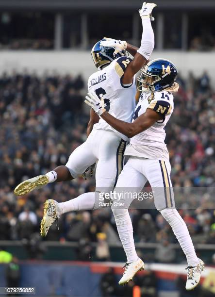 Sean Williams and Micah Farrar of the Navy Midshipmen jump in the air during the first quarter of the game against Army Black Knights at Lincoln...
