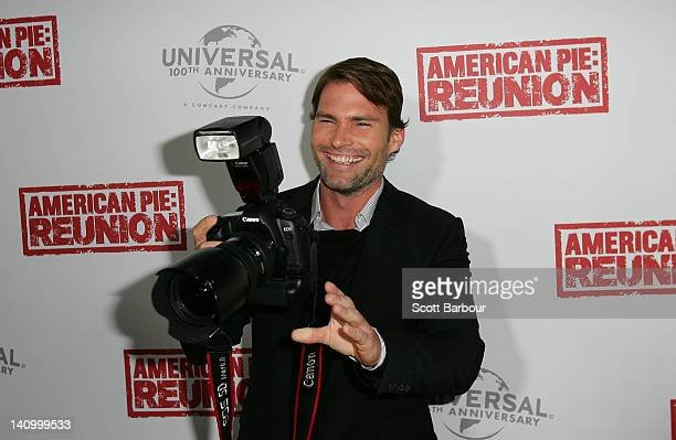 Seann William Scott takes a camera from a photographer as he arrives at the Australian premiere of American Pie Reunion on March 7 2012 in Melbourne...