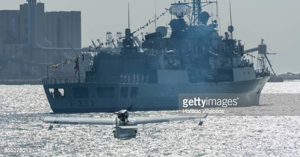 A seaplane flies over Tagus River near Portuguese Navy frigate NRP Alvares Cabral during the commemoration of the 100th anniversary of Portuguese...