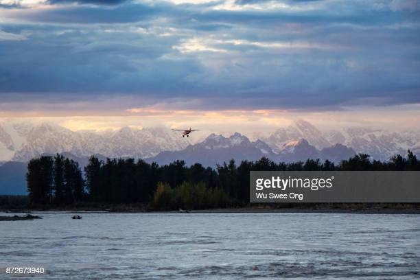 Seaplane flying over Alaskan range during sunset