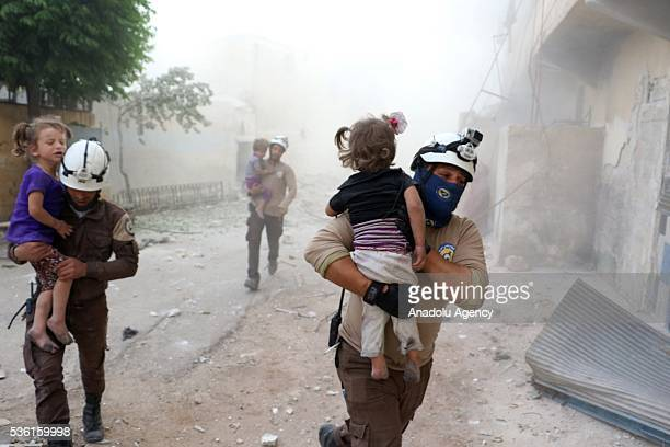 Searc and rescue team members carry wounded kids after Assad forces' airstrike hit residential areas in Tal Zarazir Neighborhoof of Sukkeri District...