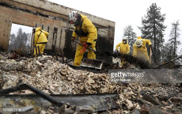 Search and rescue crews dig through the burnt remains of a business as they search for human remains on November 21 2018 in Paradise California...