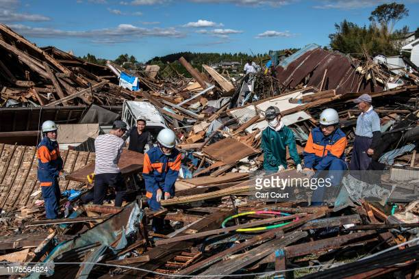 Search and rescue crews salvage belongings from the debris of buildings destroyed by a tornado shortly before the arrival of Typhoon Hagibis on...