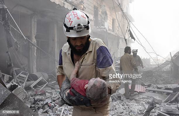 A search and rescue member carries a child from the site of a barrel bomb attack staged by Syrian army in the oppositioncontrolled Mashhad district...