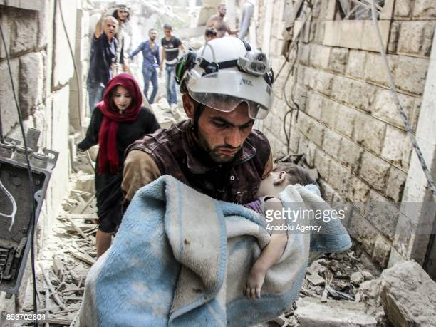 A search and rescue member holds a baby wrapped with a blanket after Assad Regime's forces carried out air strikes over the deconflict zone at the...